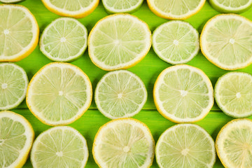 Slices of limes and lemons on green wooden table