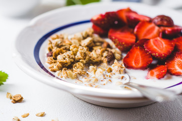 Muesli with milk and fresh strawberry in a white plate