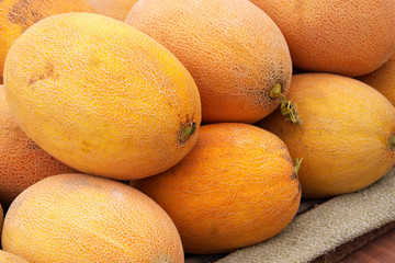 Yellow tasty juicy melons on the market. Fruit background