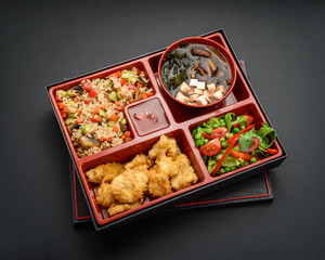 Japanese cuisine. Bento. Miso soup , rice chicken and salad. Concrete background.