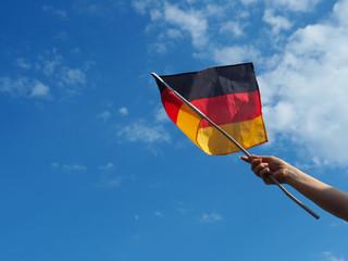 Junge Frau winkt mit deutscher Fahne