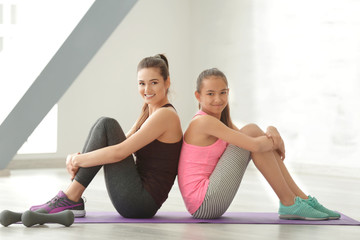 Mother and daughter sitting in gym