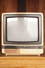 Retro old television in vintage wooden wall brown background.