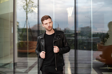 Cool young European male with bristle and stylish haircut standing outside office building with glass door, having confident look, adjusting his trendy black leather jacket. People and style concept
