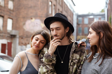 Stylish bearded guy having thoughtful look, holding hand in chin, facing dilemma as he has to choose between two gorgeous beautiful females who standing close to him, trying to attract his attention