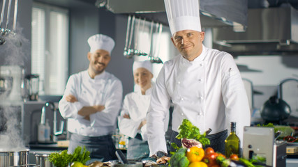 Famous Chef of a Big Restaurant Prepares Dishes and Smiles On Camera. In the Background Two Apprentices and Modern Kitchen.
