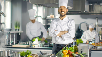 Canvas Prints Cooking Famous Chef of a Big Restaurant Crosses Arms and Smiles in a Modern Kitchen. His Staff in Working in the Background.