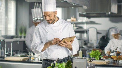 Famous Chef Uses Tablet Computer for Recipes While Working in a Modern Kitchen. His Help Work in the Background.
