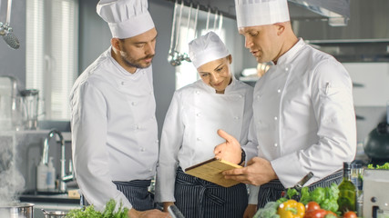 In the Modern Kitchen Team of Cooks Use Tablet Computer For Recipes, They Smile and Have Discussion. Kitchen is Full of Food Ingredients, Vegetables, Meat, Boiling Soup.