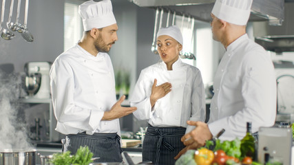 In the Modern Kitchen Team of Cooks Have Discussion. Kitchen is Full of Food Ingredients, Vegetables, Meat, Boiling Soup.