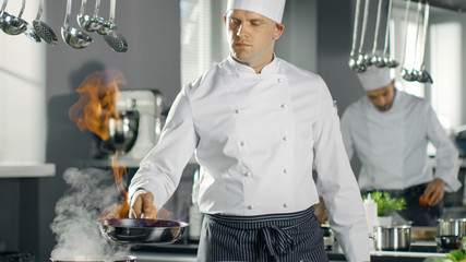Professional Chef Fires up Oil on a Pan. Flambe Style Cooking. He Works in a Modern Kitchen with Lots of Ingredients Lying Around.