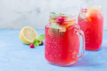 Summer Berry Drink. Lemonade with raspberry lemon, mint in mason jar on blue stone table background. Copy space, horizontal image