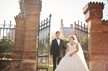 Newly married couple posing next to the gates on their wedding day.