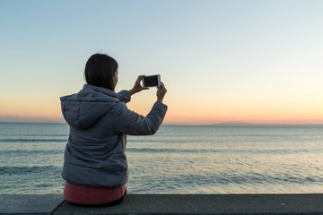 Woman taking photon with seascape and sunset