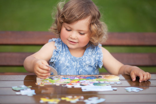 Adorable happy little child playing with puzzle