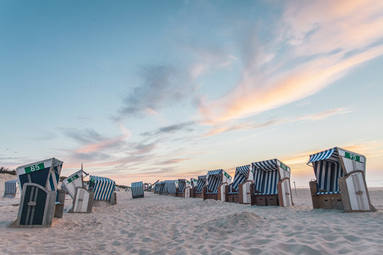 Beach chairs on the island Nordernery in the North Sea during the sunset