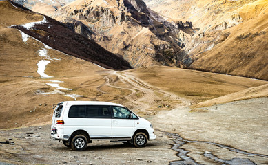 White van ready to travel through steep trail in Kazbegi, Stepantsminda, Georgia