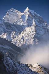Man and mountains. Nepal, Everest Region, view of Kantega peak (6,782 m) from the hill near Pheriche village (4,371 m).