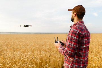 Farmer holds remote controller with his hands while copter is flying on background. Drone hovers behind the agronomist in wheat field. Agricultural new technologies and innovations. Back view