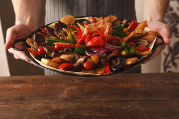 Presentation dish with stewed meat, different kind of vegetables, field mushrooms, laid on lavash and big copper plate, and decorated with sliced onion and pepper. Meal in hands