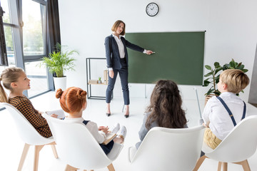 young female teacher pointing at chalkboard while explaining lesson to students