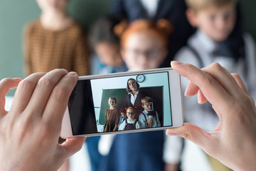 close-up view of young female teacher and cute little students photographing with smartphone