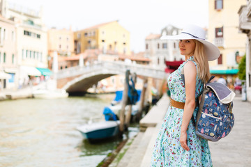 Travel tourist woman with backpack in Venice, Italy. girl on vacation smiling happy by Grand Canal. girl having fun traveling outdoors.