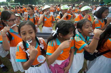 Student brush their teeth as they gather on an oral and dental health education event for children, held by the government at Ngurah Rai sport complex in Denpasar