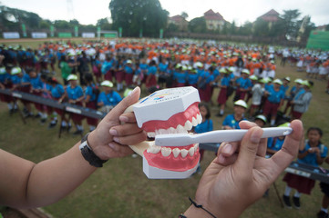 An instructor shows how to properly brush teeth during an oral and dental health education event for children, held by the government at Ngurah Rai sport complex in Denpasar