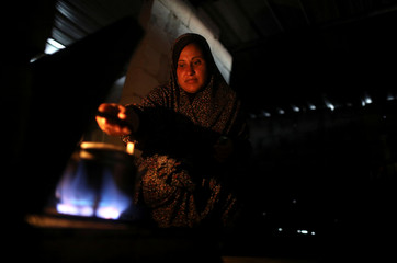 Palestinian woman makes tea as she uses candle light during power cut in the kitchen of her family house in Khan Younis in the southern Gaza Strip