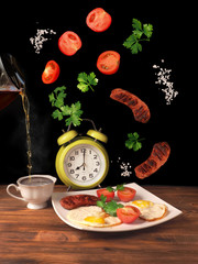 Flying sausages, tomatoes, salt, parsley. Breakfast concept