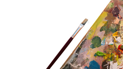a paint brush and a painting palette covered in dried up paint with the colors yellow, green, blue, red.