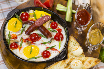 Fried eggs with cherry and sausages. Scrambled eggs with smoked sausages and cherry tomatoes in a frying pan.