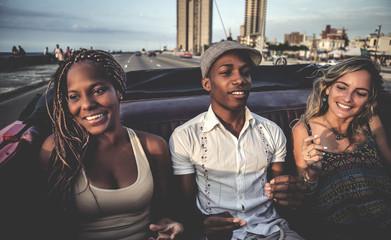 Friends riding through urban environment in open convertible classic car