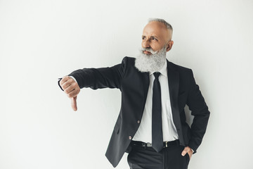 senior businessman showing thumb down on light background with angry expression