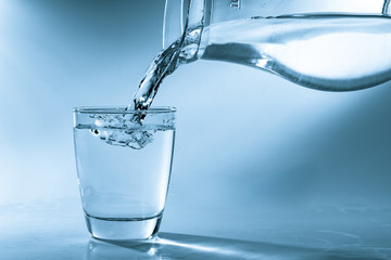 Drinking water is poured into a glass from a jug