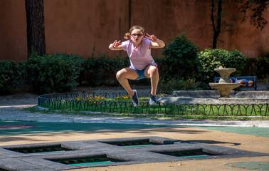Niña saltando en trampolín en un parque