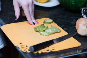 Chef's hands cut into zucchini