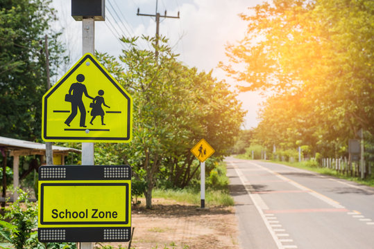 Yellow sign school zone symbol in the countryside .