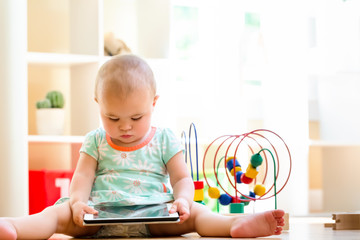 Toddler girl watching a tablet computer in her house