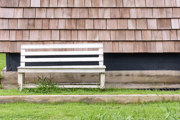 white  wooden bench lay  on grass and cedar roof
