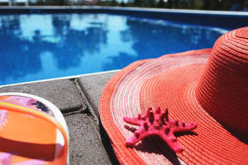 Summer accessories (hat, slaps) near the pool. With free blank space for your text.