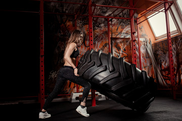 young female fitness model execute exercise with large tire casing. Woman in gym.