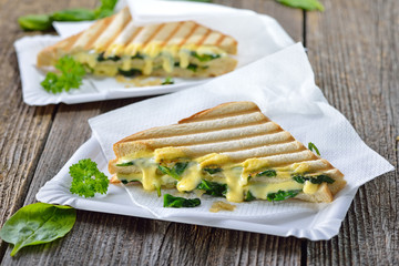 Im Kontaktgrill gepresstes italienisches Panini mit jungem Blattspinat, Zwiebeln  und Käse - Pressed and toasted double panini with spinach, onions and cheese served on paper plates