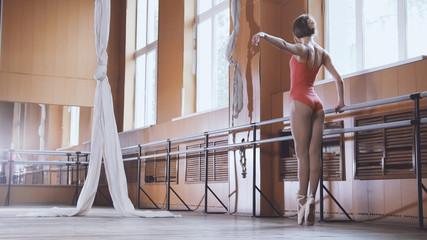 Model girl ballerina practicing in the studio