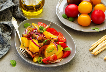 Vegetarian salad with fresh tomato, with red onion, basil and olive oil.