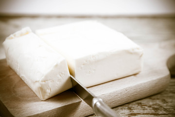Butter on a wooden chopping board  cut with a knife