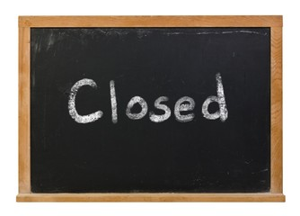 Closed written in white chalk on a black chalkboard isolated on white