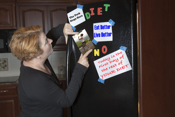Woman posting dieting motivation on refrigerator