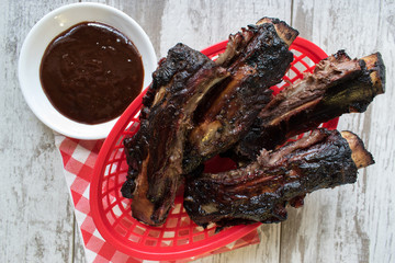Barbecued ribs in red basket with sauce on rustic white background top view